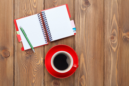 notebook page: Office desk table with supplies and coffee cup. Top view with copy space