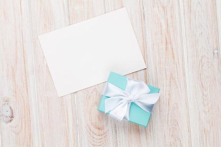 흰색 나무 테이블에 선물 상자와 빈 사진 프레임 또는 인사말 카드입니다. 평면도