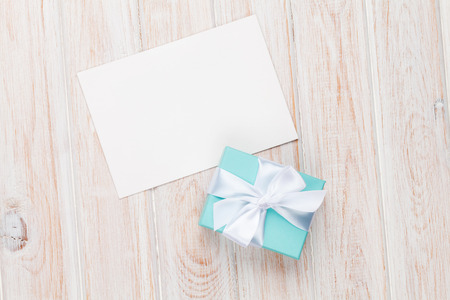 Gift box and blank photo frame or greeting card on white wooden table. Top view