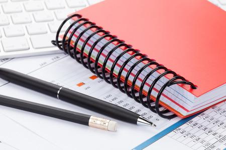 cuadro sinoptico: Escritorio de oficina con informes, equipo, suministros y libreta primer