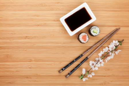 Maki sushi, chopsticks and soy sauce on bamboo wooden table background with copy space photo