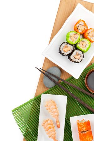 Sushi maki and shrimp sushi on bamboo board. Isolated on white background with copy space photo