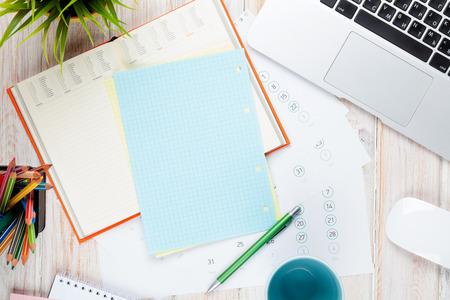 Schreibtisch Tisch mit Computer, Verbrauchsmaterial, Kaffeetasse und Blume. Ansicht von oben mit Kopie Raum