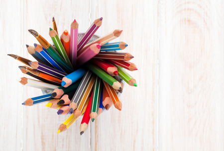 pencil holder: Colorful pencils over wooden office table with copy space