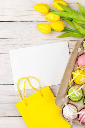 Easter background with colorful eggs, yellow tulips and greeting card over white wood. Top view with copy space photo