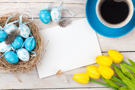 easter nest: Easter background with blue and white eggs in nest, yellow tulips and greeting card over white wood. Top view with copy space