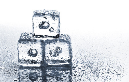 Melting ice cubes with air bubbles inside on white background with copy space photo