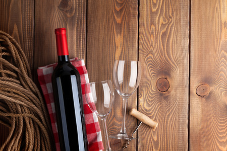 Red wine bottle, glasses and corkscrew over rustic wooden table background with copy space photo
