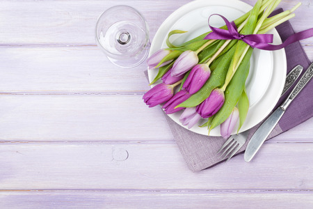 Purple tulip bouquet over plate on purple wooden table. Top view with copy space photo