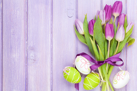 紫のチューリップの花束とイースターの卵。紫の木製テーブルの上のトップ ビュー