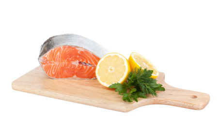 Salmon on cutting board with lemons and herbs. Isolated on white background photo
