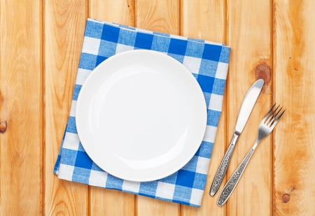 空のプレート、カトラリー、木製のテーブルの背景の上のタオル。コピー スペースを上から表示します。