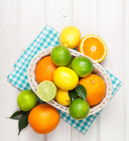 canasta de frutas: Las frutas c�tricas en la cesta. Las naranjas, limas y limones. Sobre blanco mesa de madera de fondo Foto de archivo