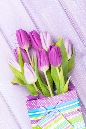 Purple tulip bouquet in gift bag over wooden table photo