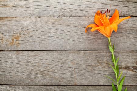 コピー スペースを木製のテーブル背景にオレンジ色のユリの花