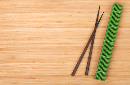 Chopsticks and bamboo mat on table with copy space