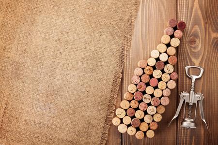 Botella de vino en forma de tapones de corcho y sacacorchos más rústico fondo de la tabla de madera y arpillera. Vista superior con espacio de copia