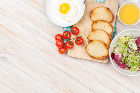 breakfast plate: Healthy breakfast with fried egg, toasts and salad on white wooden table. Top view with copy space