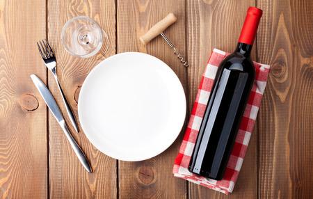 Tabel met lege plaat, glas wijn en een fles rode wijn. Bovenaanzicht over rustieke houten tafel achtergrond