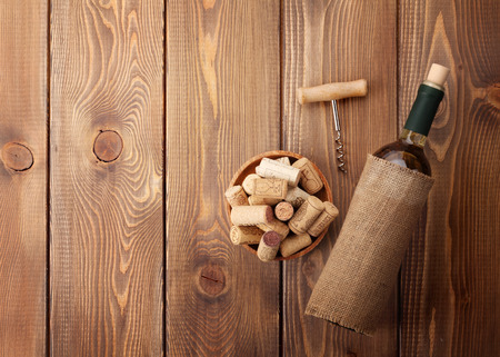 white wine bottle: White wine bottle, corks and corkscrew over wooden table background. Top view with copy space Stock Photo