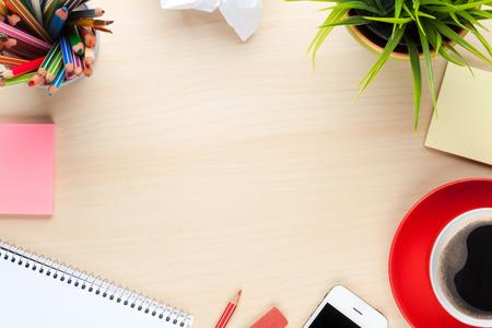 Kancelářský stůl stůl se zásobami, šálek kávy a květiny. Pohled shora s kopií vesmíru