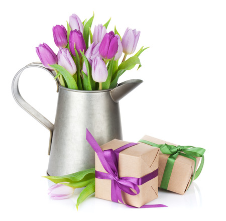 Purple tulip bouquet in watering can and gift boxes. Isolated on white background photo