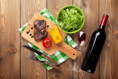 Steak with grilled corn, salad and red wine over wooden table. Top view