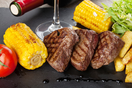 grilled potato: Steak with grilled potato, corn, salad and red wine closeup