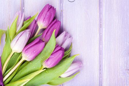 tulipan: Fioletowe tulipany na drewnianym stole. Widok z góry z miejsca na kopię
