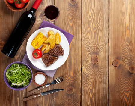 Steak with grilled potato, corn, salad and red wine over wooden table. Top view with copy space