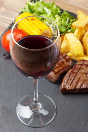 grilled potato: Red wine glass and steak with grilled potato, corn, salad on stone plate