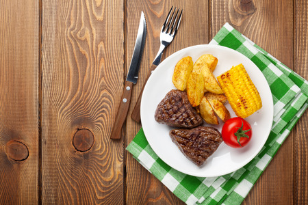 grilled potato: Steak with grilled potato, corn, salad and tomato over wooden table. Top view with copy space