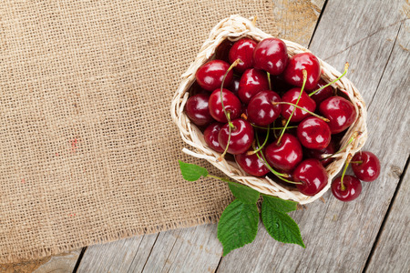 basket: Ripe cherries on wooden table. View from above with copy space
