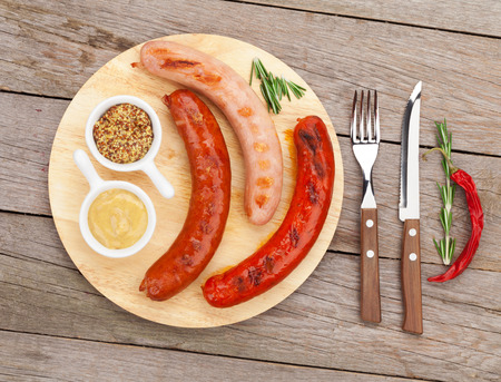 condiments: Various grilled sausages with condiments on cutting board