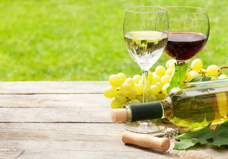 racimos de uvas: Blanco y rojo copas de vino, botella de vino y la uva blanca en la mesa de madera con espacio de copia
