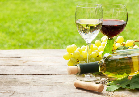 green bottle: White and red wine glasses, wine bottle and white grape on wood table with copy space