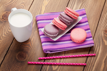 Colorful macaron cookies and cup of milk on wooden table background photo