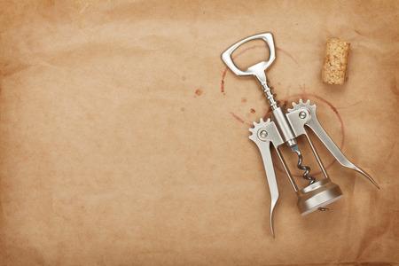 Kurk en kurkentrekker met rode wijn vlekken op bruine papieren achtergrond met kopie ruimte