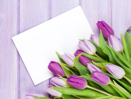 ''greeting card'': Purple tulip bouquet and blank greeting card. Top view over wooden table