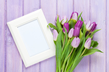 april flowers: Purple tulip bouquet and blank photo frame. Top view over wooden table