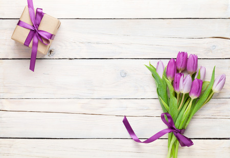 table top: Purple tulips and gift box over wooden table. Top view with copy space