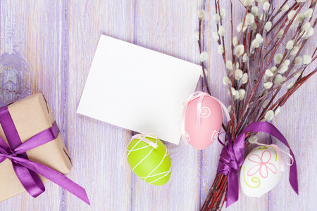 Greeting card, pussy willow and easter eggs over wooden table background with copy space Stock Photo