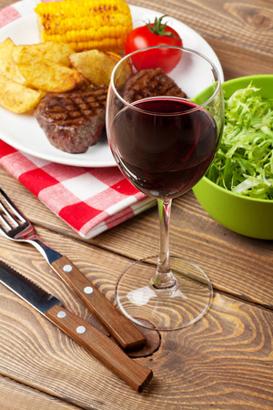 grilled potato: Glass of red wine, steak with grilled potato, corn and salad on wooden table