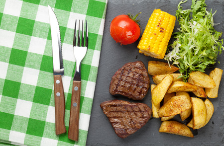 grilled potato: Steak with grilled potato, corn and salad. Top view Stock Photo