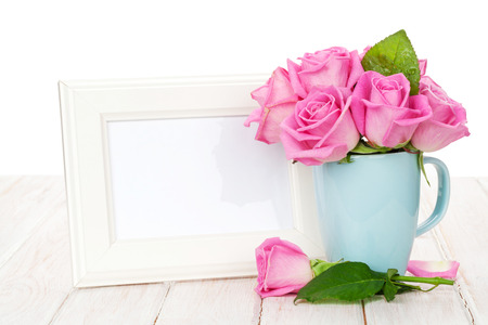 wedding table decor: Blank photo frame and pink roses bouquet in tea cup. Over wooden table
