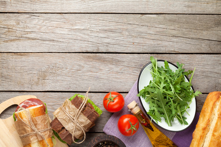 sandwich: Two sandwiches with salad, ham, cheese and tomatoes, salad and spices on wooden table. Top view with copy space Stock Photo