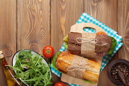 ham sandwich: Two sandwiches with salad, ham, cheese and tomatoes on wooden table. Top view with copy space