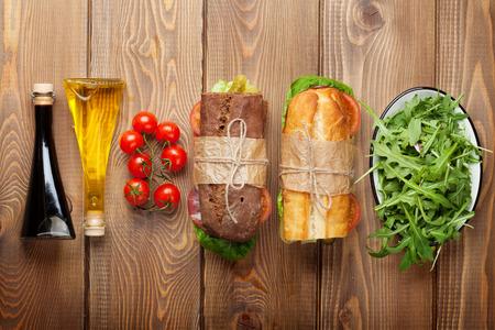 jamon y queso: Dos emparedados con ensalada, jam�n, queso y tomate, ensalada y especias en la mesa de madera. Vista superior con espacio de copia Foto de archivo