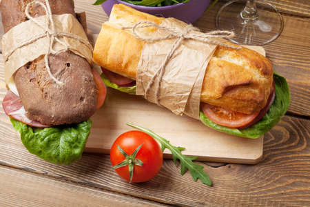 ham sandwich: Two sandwiches with salad, ham, cheese and tomatoes on wooden table