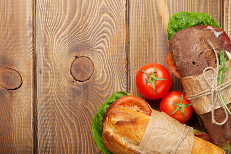 Two sandwiches with salad, ham, cheese and tomatoes on wooden table. Top view with copy space